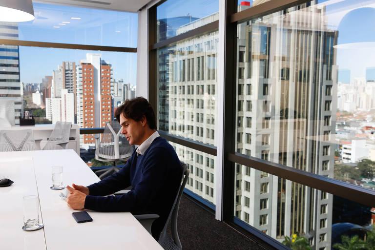 Retrato de Guilherme Benchimol, fundador e presidente da XP, sentado em seu escritório, com a cidade de São Paulo ao fundo