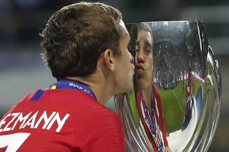 Homem com camisa vermelha beija taça de prata