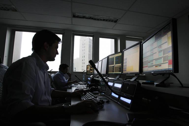 Operadores da  XP Investimentos, acompanham o fechamento da Bolsa de Valores