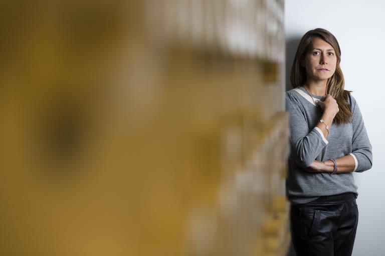 Aline Sun, sócia da Guide, de pé, ao lado de uma parede amarela