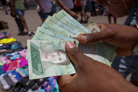 A Venezuelan man shows Venezuelan bolivar bills as she sells products in Norte de Santander Department, Colombia, on the border with San Antonio del Tachira, Venezuela, from where hundreds are crossing through the Simon Bolivar international bridge on August 19, 2018. - Bogota said on August 17 it was