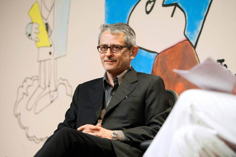 Otavio Frias Filho sentado; ao fundo, mural colorido