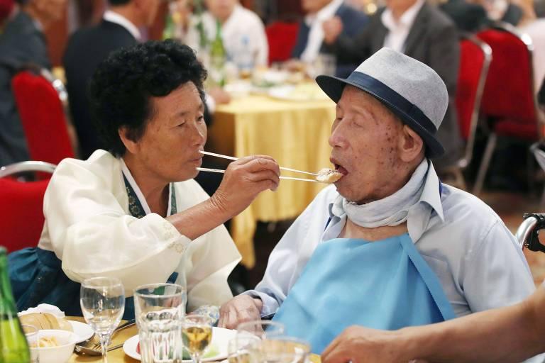 Ahn Jong-ho, 100, que mora na Coreia do Sul, recebe comida de sua filha, Ahn Jong-soon, 70, que vive no Norte, no primeiro reencontro entre eles em seis décadas