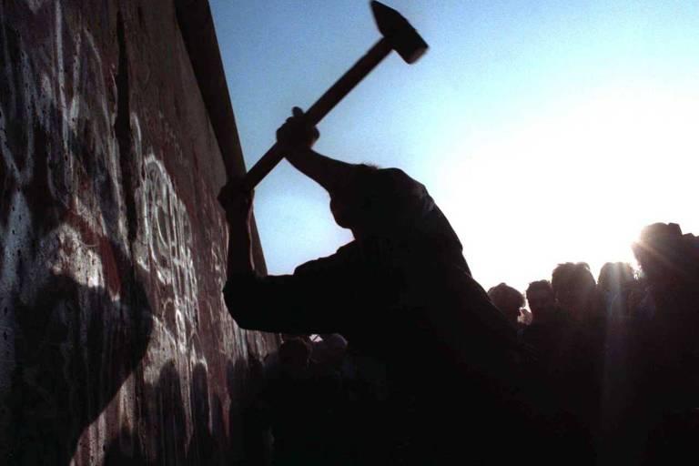 Homem desfere marteladas no muro após a abertura da fronteira entre Berlim Ocidental e Oriental em 1989