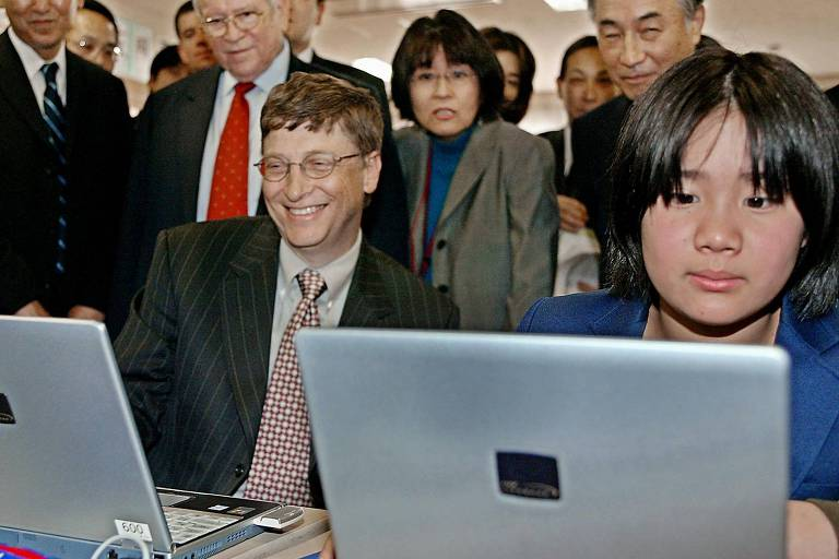 Sentados com várias pessoas em volta, jovem garoto olha para a tela do computador ao lado de Bill Gates, que está sorrindo de terno e gravata