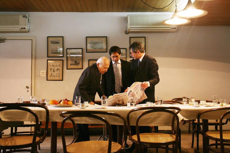 Otavio Frias Filho (à di.) segura uma página da Folha e fala com o irmão, Luiz Frias, ao centro, enquanto o pai, Octavio Frias de Oliveira, observa, atento, a página do jornal disposto sobre a mesa com louças do almoço
