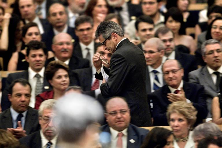Otavio Frias Filho, de pé, passa diante da então presidente Dilma Rousseff e do governador Geraldo Alckmin, entre outros políticos sentados na plateia da Sala São Paulo, visto fora de foco