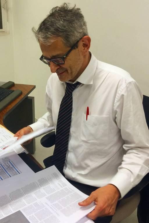 Otavio Frias Filho, sentado em sua mesa e sem terno, examina páginas impressas do jornal para aprovação