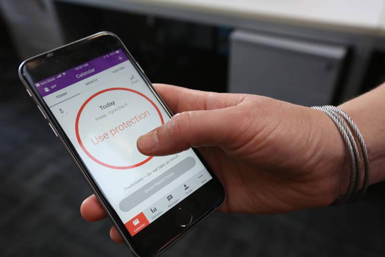 """Mulher mostra aplicativo com a mensagem """"Use Proteção"""", o que demonstra se tratar de um período fértil"""