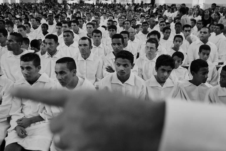 Homens vestidos de branco em bancos de igreja