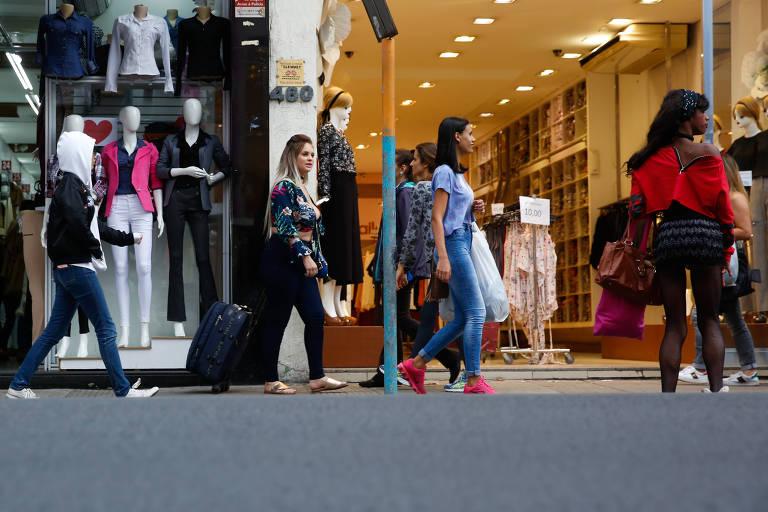 Pedestres caminham em rua comercial em São Paulo