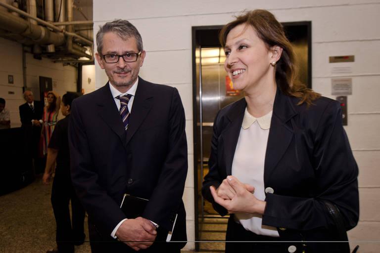 Otavio, de terno, acompanha Maria Cristina, de blusa clara e casaco, que sorri ao falar com interlocutores fora de quadro, enquanto ele olha a câmera