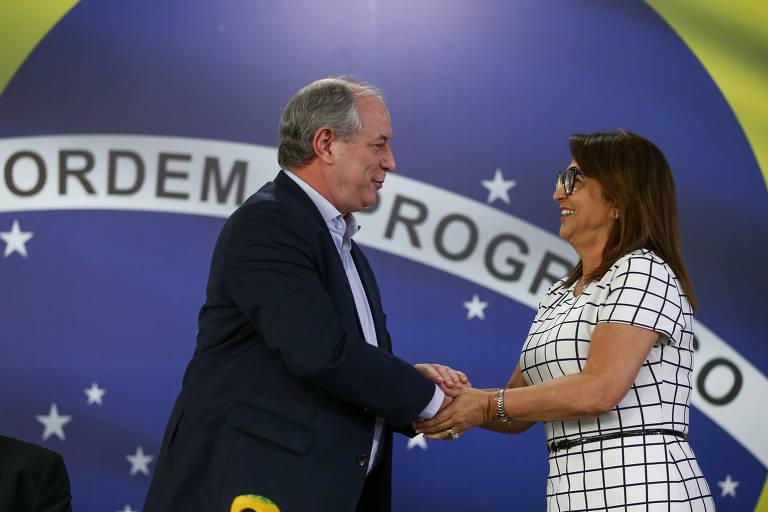 """Ciro Gomes, vestindo terno escuro, de perfil e em pé, à esquerda, cumprimenta Katia Abreu, vestindo vestido em xadrez branco, de perfil e em pé, à direita. Ao fundo, a parede é revestida com uma bandeira do Brasil, onde se lê a frase """"Ordem e Progresso""""."""