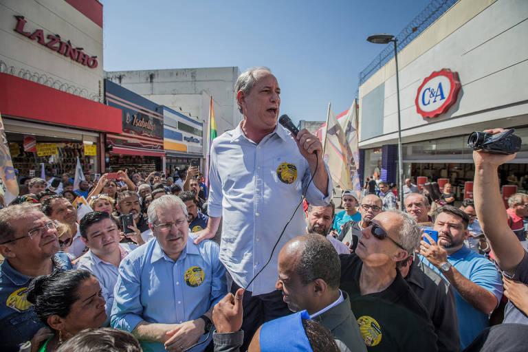 Em dia ensolarado, Ciro Gomes, vestido de camisa azul claro, com mangas arregaçadas e adesivo de campanha no peito, fala ao microfone para apoiadores na rua.