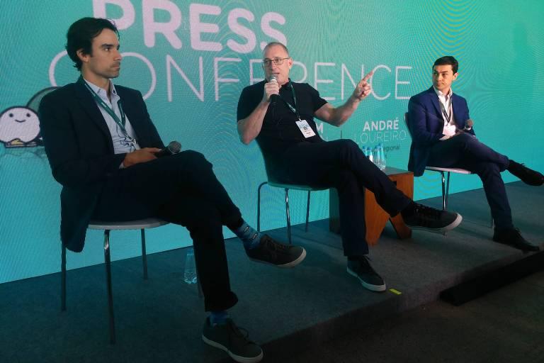 Três executivos do Waze sentados com microfones em palco durante entrevista para imprensa