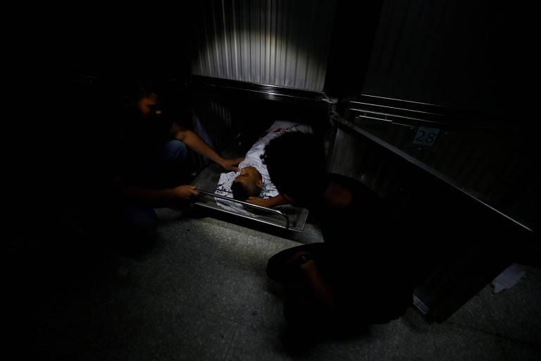 Parentes olham o corpo de Othman Helles, 15, morto durante manifestação na fronteira de Gaza com Israel