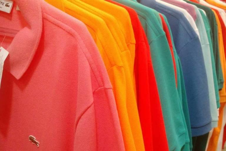 Camisas da Lacoste coloridas penduradas em arara