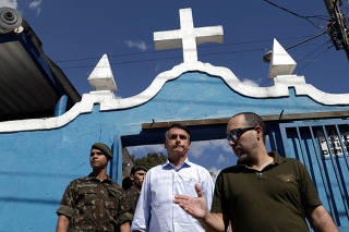 Presidential candidate Jair Bolsonaro (C) leaves the burial of Brazilian Corporal Fabiano de Oliveira Santos, who was shot dead during an operation against drug gangs in Alemao slums complex, in Japeri, near Rio de Janeiro