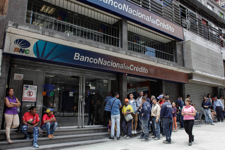 Venezuelanos aguardam em fila do lado de fora de um banco em Caracas nesta terça (21)