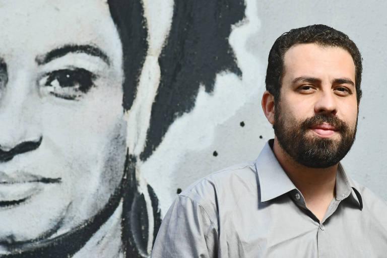 O candidato do PSOL ao Planalto, Guilherme Boulos, em frente a um grafite da vereadora assassinada Marielle Franco, na sede do partido em São Paulo