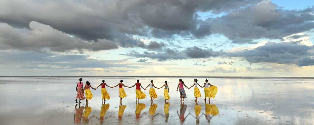 Dez meninas de mão dada de costas para a foto em praia com espelho d'água que reflete o céu com nuvens. Oito estão com saias rodadas amarelas e duas com saias rodadas rosas com estampa