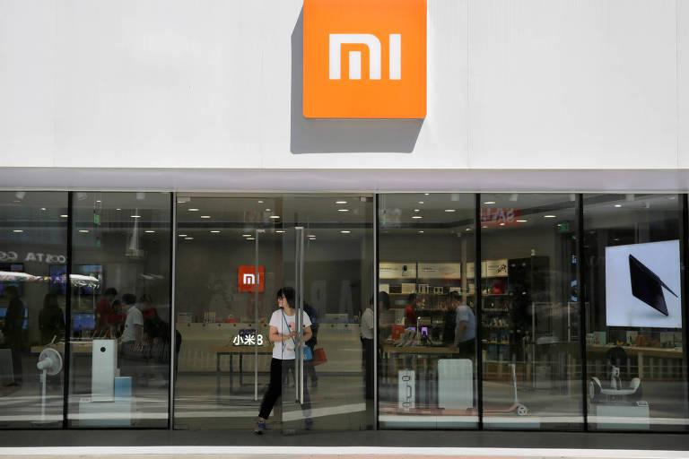 Cliente sai em porta de vidro da loja da Xiaomi em Pequim num dia ensolarado
