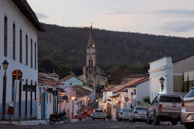 Rua de pedra em cidade histórica, com carros e igreja ao fundo