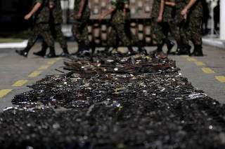 Brazilian  soldiers walk past guns seized from criminals by the armed forces before being destroyed in Rio de Janeiro