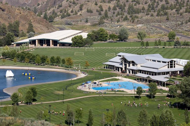 Foto de casarão com grande piscina e campos gramados ao redor