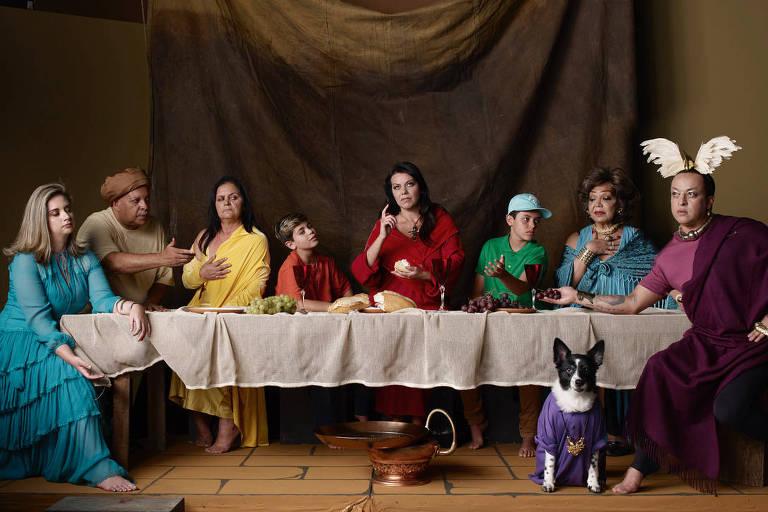 Personagens sentados em torno de longa mesa de jantar simulando cena similar à Santa Ceia