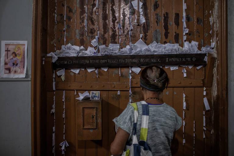 Senhora de costas com porta de madeira cheia de bilhetes de papel