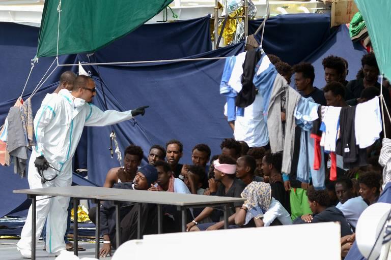 Imigrantes aguardam dentro do barco Diciotti, da guarda costeira italiana, por uma definição de onde vão poder desembarcar