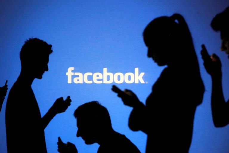 Sombra de pessoas olhando para os celulares com logo do Facebook atrás