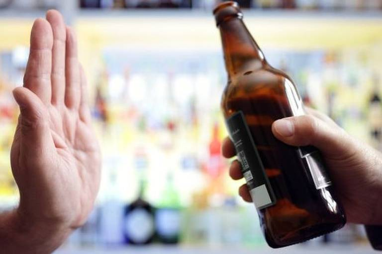 Mão faz sinal de 'pare' para garrafa de cerveja