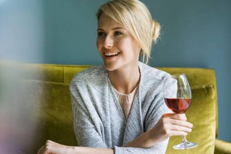 Mulher bebe taça de vinho