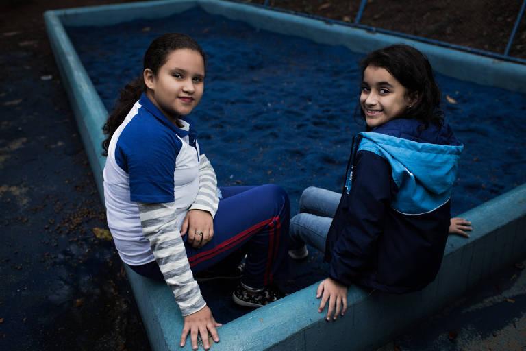 Duas crianças sentam na estrutura de concreto da caixa de areia azul da escola