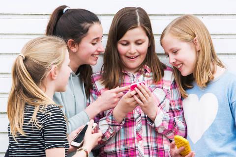 Group Of Young Girls Outdoors Looking At Message On Mobile Phone DIREITOS RESERVADOS. NÃO PUBLICAR SEM AUTORIZAÇÃO DO DETENTOR DOS DIREITOS AUTORAIS E DE IMAGEM