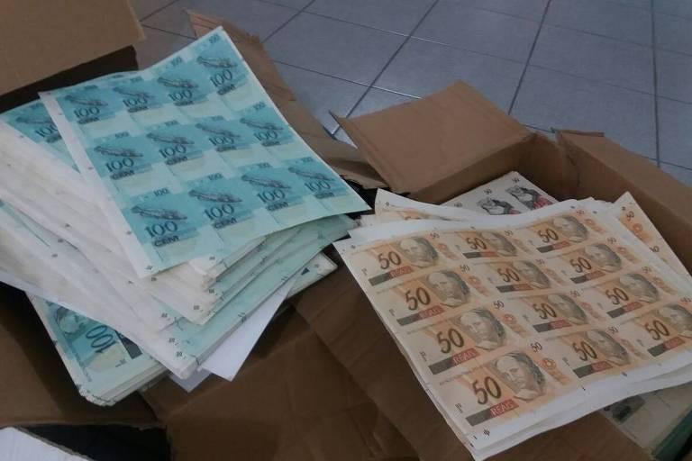 Caixas com notas falsas de R$ 100 e de R$ 50