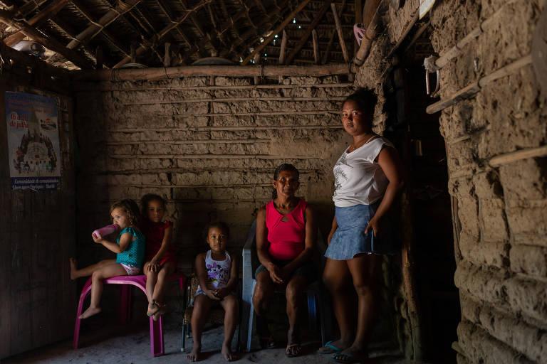 A luz não chegou ainda na casa da agricultora Maria Vitória Gonçalves, 56 (vermelho), também em Brejinho, zona rural de Buriti (MA). Ela vive com a filha Maria de Fátima, 16 (à direita), e as netas Taíla Vitória, 2 (mamadeira); Aila, (vestido vermelho) e Osllen Thalia, 5.
