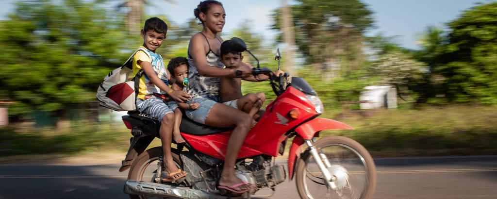 Moto em movimento com uma mulher guiando e três crianças