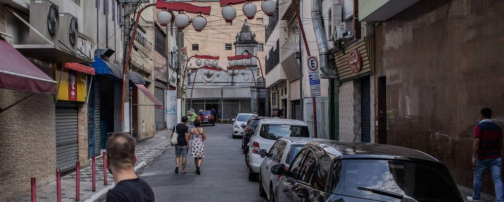 igreja ao fundo de beco com carros parados e lanternas japonesas