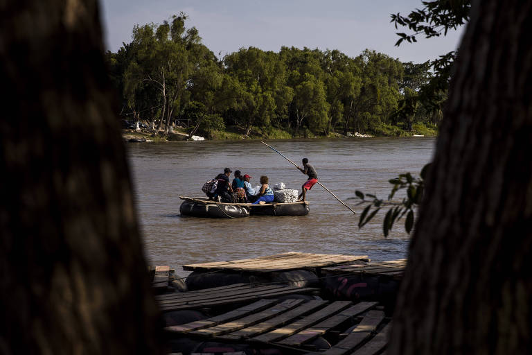 Balsas com migrantes cruzam clandestinamente o rio Suchiate, na fronteira entre México e Guatemala