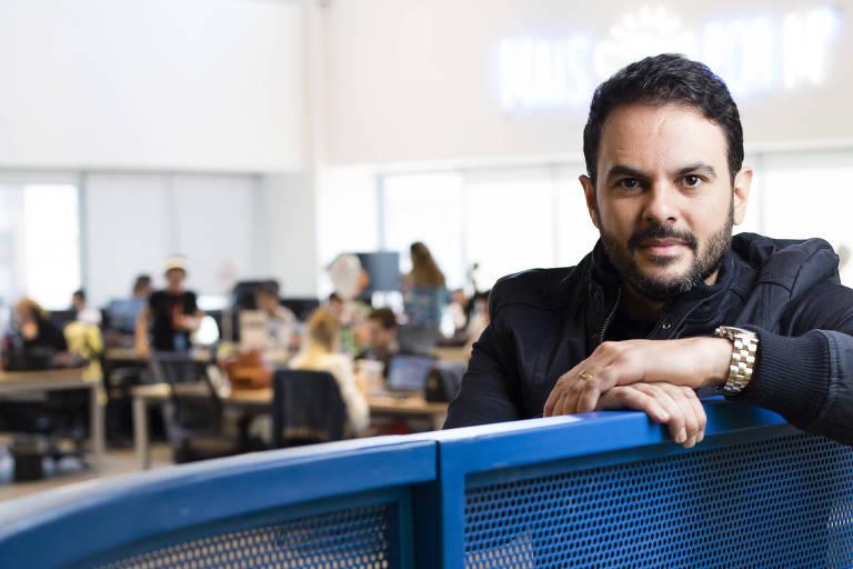 Fábio Rodrigues, sócio da startup Novidá, sentado com as mãos cruzadas sobre encosto de ferro azul