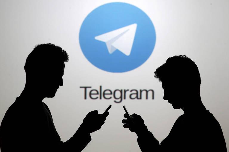 Silhueta de dois usuários de celular com o logotipo do aplicativo Telegram ao fundo
