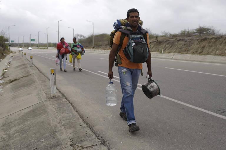 Venezuelanos caminham por rodovia peruana após cruzar a fronteira com o Equador, perto de Tumbes, no norte do Peru