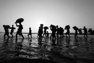 Rohingya refugees walk through water after crossing the Bangladesh-Myanmar border, at a port in Teknaf