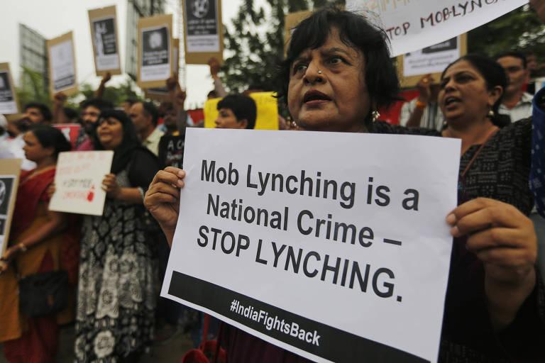"""""""Parem de linchar"""", diz cartaz segurado por indiana durante protesto em Ahmedabad, no noroeste da Índia"""