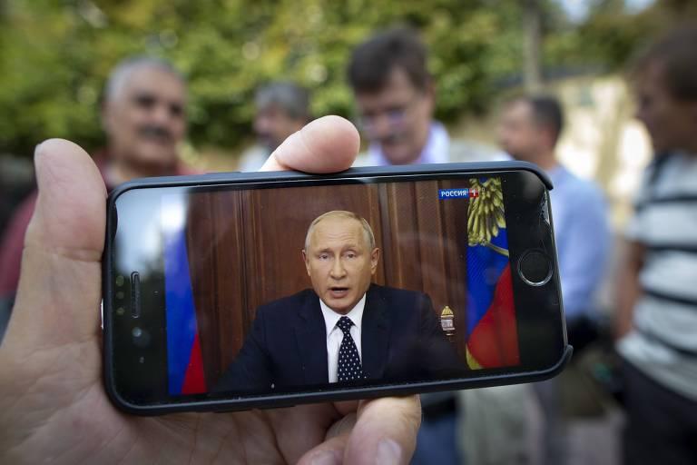 Foto mostra homem segurando celular transmitindo discurso de Valdimir Putin sobre reforma da Previdência na TV estatal russa, nesta quarta, em Moscou