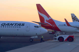 Workers are seen near Qantas Airways, Australia's national carrier, Boeing 737-800 aircraft on the tarmac at Adelaide Airport