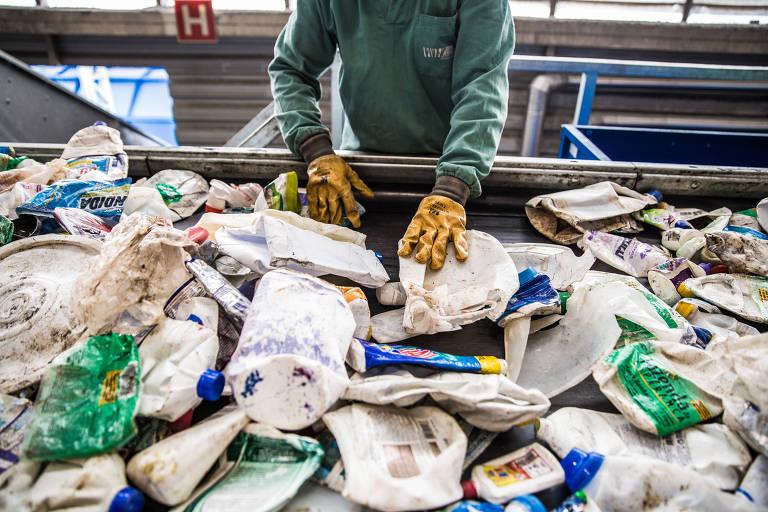 Mãos com luvas amarelas separam lixo